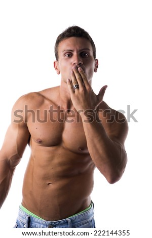 Sexy handsome shirtless man with a muscular physique standing blowing a kiss with his hand to his mouth or hiding a guilty expression, isolated on white