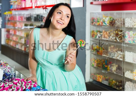 sexy happy girl posing in the store with lolly on the background of counters with sweets
