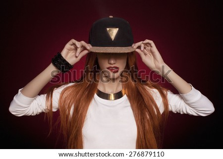 Sexy hip-hop woman in cap with long red hair. Fashion portrait of modern girl in cap #276879110