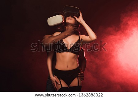 sexy interracial couple in virtual reality headsets on dark with red smoke
