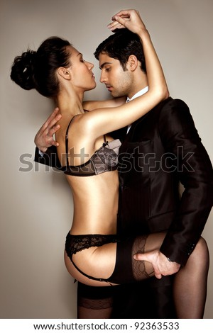 Sexy lady in black lingerie and businessman in suit in passionate embrace