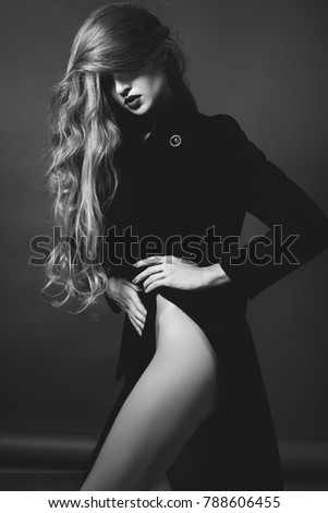 Sexy lady in Elegant Coat. Beautiful model in Fashion Jacket with Long Curly Hair. Erotic style. Black and White shot on grey background