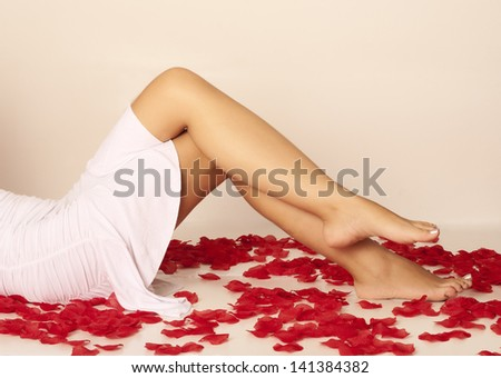 Sexy legs of a woman surrounded with rose petals