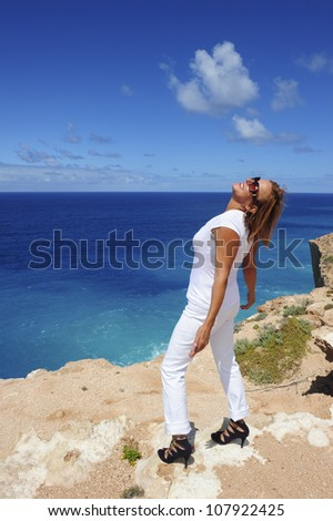 Sexy looking mature woman dressed in white and purple high heel shoes is standing at the edge of a cliff overlooking the ocean, isolated with the sea and blue sky as background and copy space.