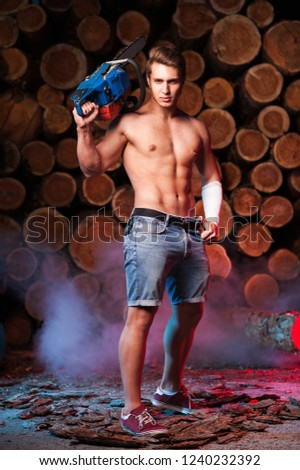 Sexy lumberjack without outerwear with a chainsaw in hand against the background of firewood