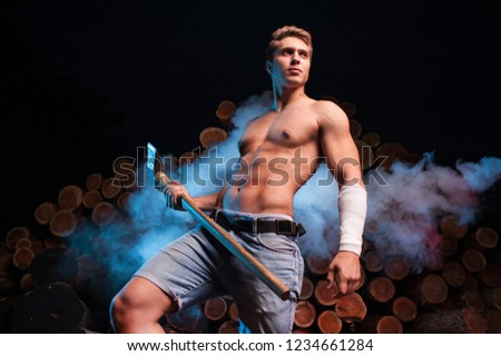 Sexy lumberjack worker with an ax in his hands against the background of firewood