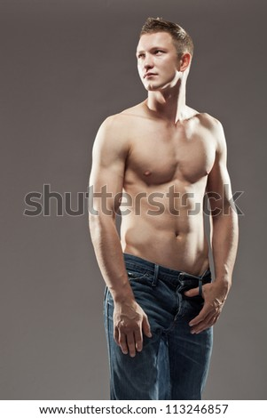 Sexy macho shirtless man with a muscular body posing in jeans with his one thumb hooked in the belt loops