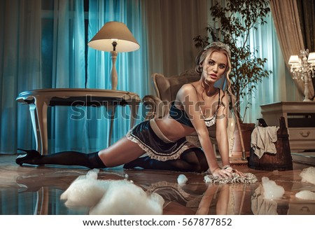 Sexy maid cleaning the floor in a stylish interior