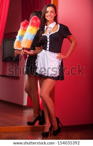 Sexy maid. Full length of beautiful young maid holding brush and looking at camera