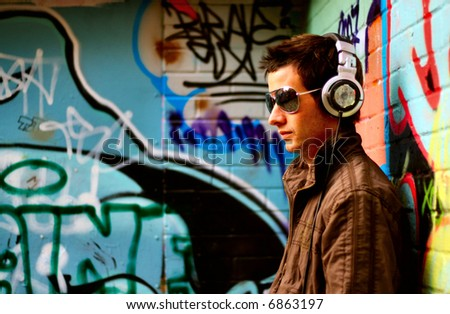 Sexy male DJ pose infront of graffiti