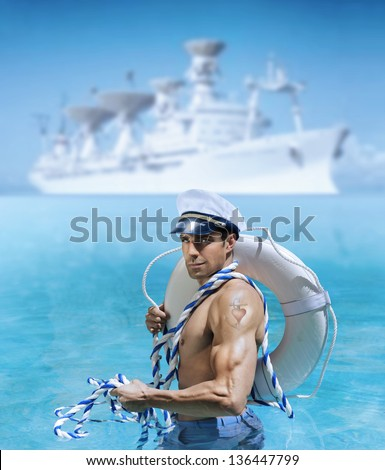 Sexy male model as sailor flexing his bicep in front of ship at port with a heart tattoo on his arm