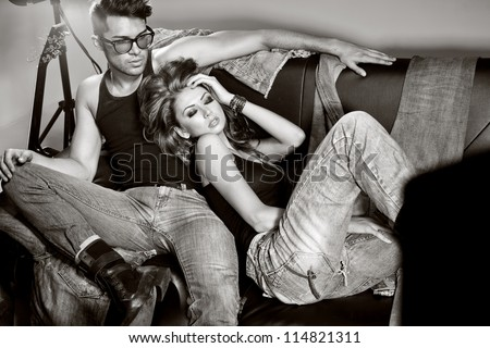 Sexy man and woman doing a fashion photo shoot in a professional studio - stock photo