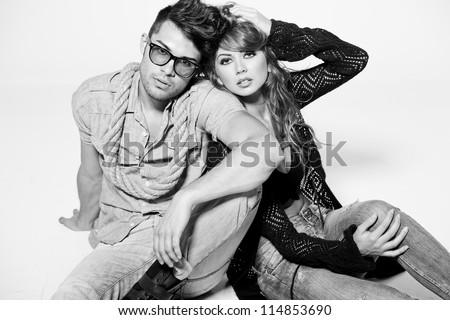 Sexy man and woman doing a fashion photo shoot in a professional studio - bw retro mood