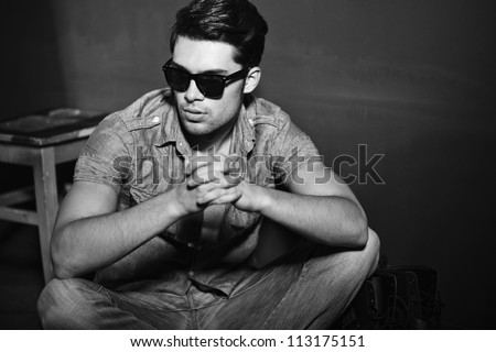 Sexy man looking cool - vintage stylized black and white photo (Photo has an intentional film grain)