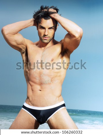 Sexy man posing against summer background