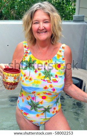 stock photo : Sexy mature female enjoying her morning coffee in her hot tub.