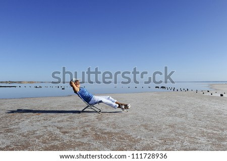 Sexy mature woman sitting relaxed at salt lake in remote outback Australia, wearing high heels and and white rimmed summer hat, isolated with water and sky as background and copy space.