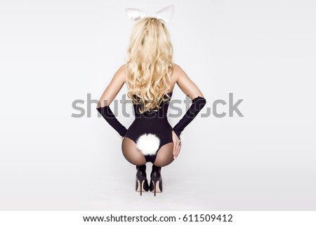 Sexy model dressed in costume Easter bunny, standing on a white background and sensually posing #611509412