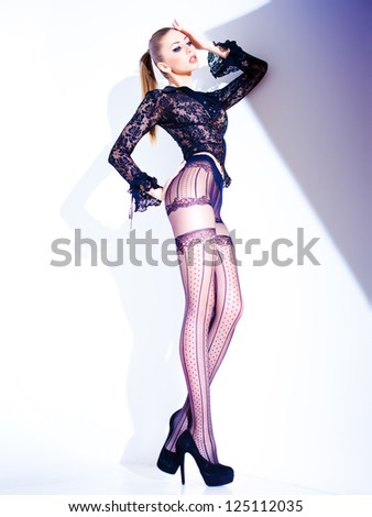 sexy model with long legs dressed in lace blouse and elegant tights posing - fashion shoot