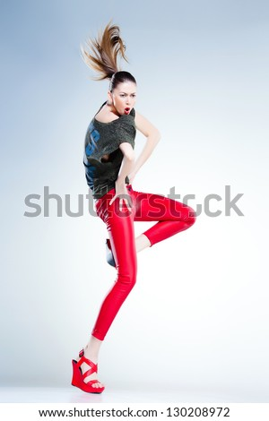 sexy model with slim body dressed in red jumping and screaming in the studio against blueish background
