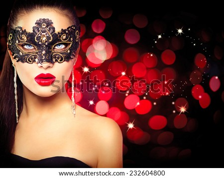 Sexy model woman in venetian masquerade carnival mask at party over holiday glowing red background. Christmas and New Year celebration. Glamour lady