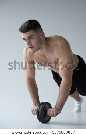 sexy muscular bodybuilder with bare torso exercising with ab wheel on grey background