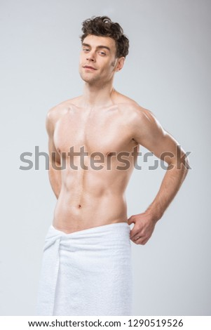 sexy muscular man posing in towel isolated on grey