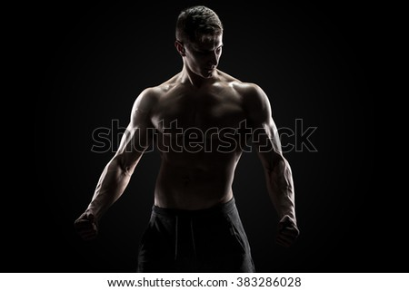 Sexy muscular man posing with naked torso on black background #383286028