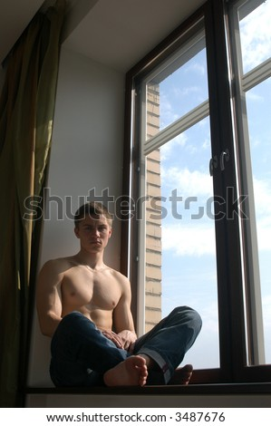 Sexy muscular man sitting on the window-sill