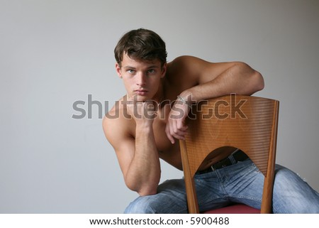 Sexy muscular man sitting on the wooden chair. Copy space