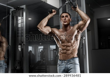 Sexy muscular man working out in gym, shaped abdominal. Strong male naked torso abs