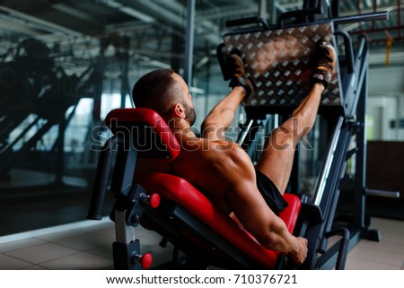 Sexy muscular men using a leg press machine and placing his legs on the platform on a dark colorful background.
