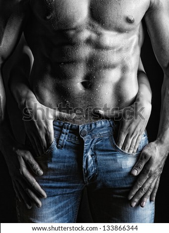 Sexy muscular naked man and female hands unbuckle his jeans on a dark background