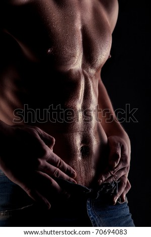 Sexy muscular naked man with water drops on stomach