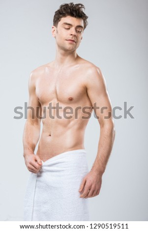 sexy muscular shirtless man posing in towel isolated on grey