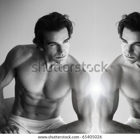 Sexy muscular young man looking in mirror