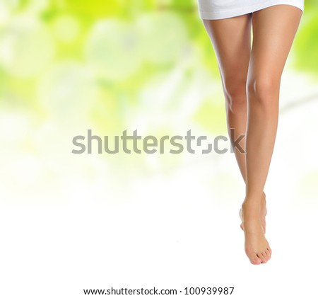 sexy naked slender female legs making step over green natural background - stock photo