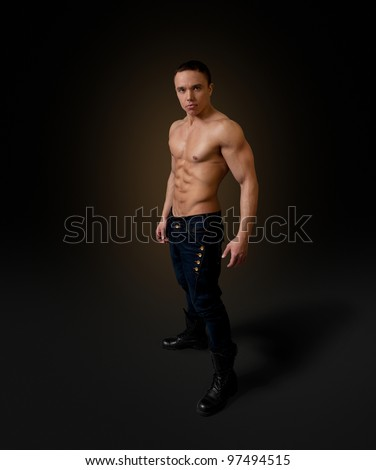 Sexy naked torso fit and neat young man studio full portrait. Wearing dark blue jeans and black boots. Fit and neat collection.