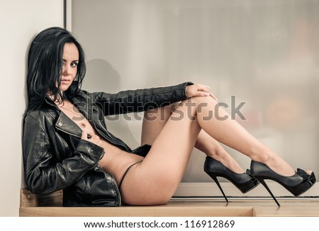 Sexy naked woman wearing high heels shoes and leather jacket posing indoors