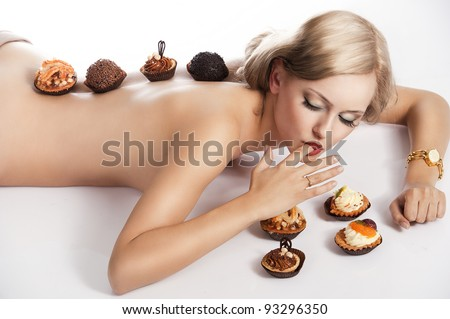 sexy naked woman with long blond hair laying down on white with some pastry near her in act to eat them, she has some pastries on her back. - stock photo