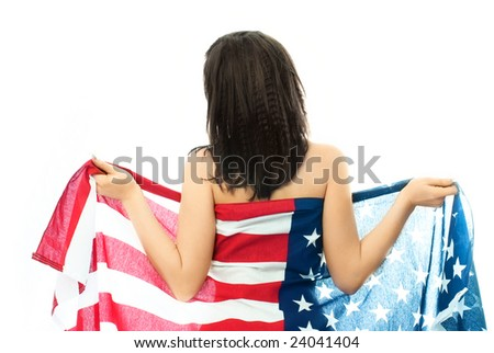 sexy nude brunette woman wearing an American flag standing with her back to us and unwrapping the flag
