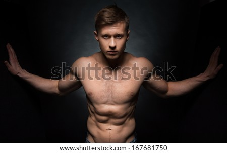 Sexy nude fit male model posing on camera. Standing with wide open hands isolated over black background
