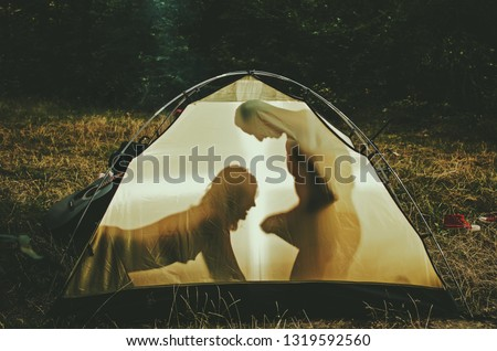 Sexy nude, topless woman sits on male knees. Outdoor sex concept. Couple full of desire going make love outdoor. Couple in love at picnic with fire in forest, trees on background. Sensual.