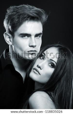 Sexy passion couple, beautiful young man and woman closeup, studio shot toned blue