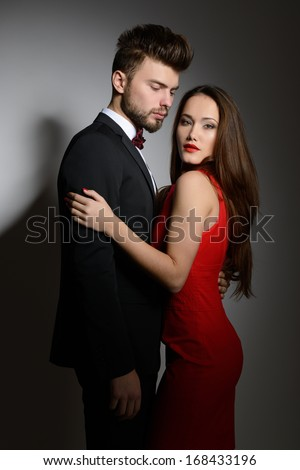 Sexy passion couple in love. Portrait of beautiful young man and woman dressed in classic clothes, studio shot over grey background