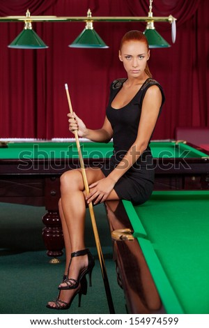 Sexy pool player. Beautiful young female pool player in black dress holding cue and looking at camera