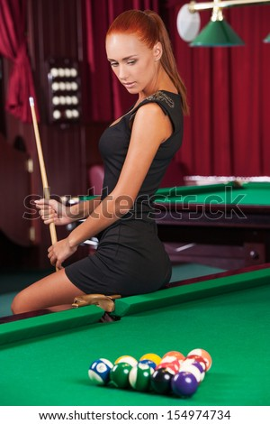 Sexy pool player. Beautiful young female pool player in black dress holding cue and looking at the billiard table