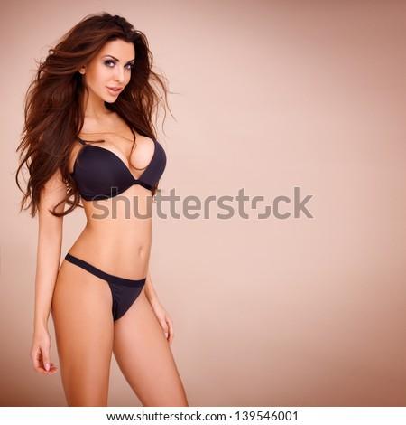 Sexy pose of a dark haired woman wearing a black bikini
