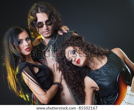 sexy rocker group with an electric guitar, studio shot