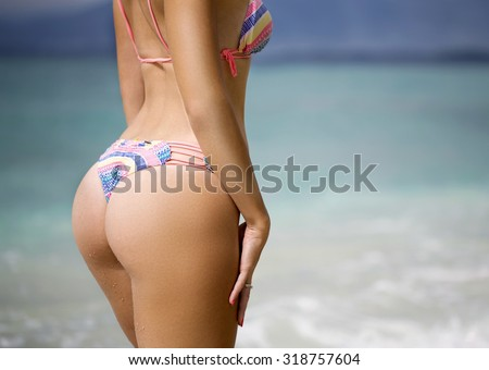 Sexy sandy woman buttocks on the beach background #318757604
